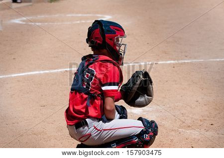 American youth baseball catcher behind home plate waiting on pitch.