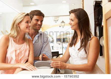 Female Sales Assistant At Checkout Of Clothing Store With Customers