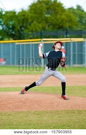 Young teen boy on the pitching mound during wind up.