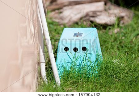 Blue septic control box outdoors next to home.
