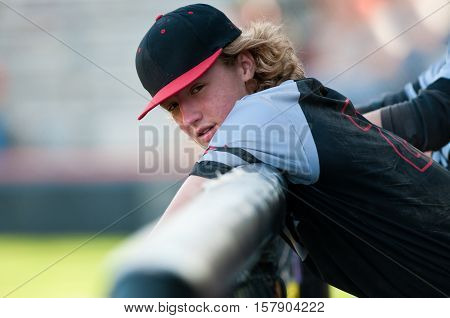 American high school boy in the dugout during a game.