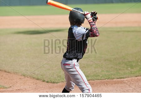 Teenage boy standing at home play ready to bat.