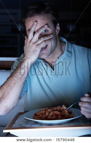Frightened Man Enjoying Meal Whilst Watching TV