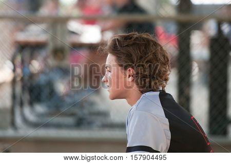 Youth baseball boy sitting in dugout looking sideways.
