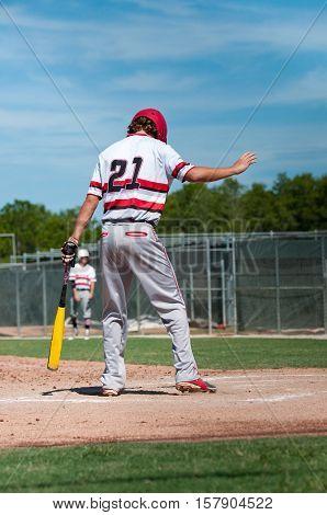 Teen baseball boy standing on home plate ready to bat.