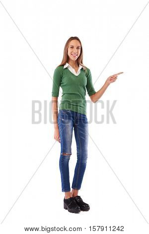 Full-length studio shot of gentle girl who is showing the way and pointing with finger to indicate direction