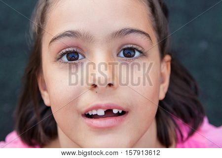 Closeup of girl with tooth missing looking at camera