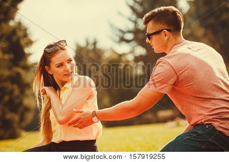 Love romance heartbreak sadness concept. Upset lady rejects her man. Lady shows her anger to boyfriend in park.