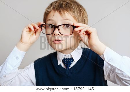 little Boy in eyeglasses in a white shirt, tie and vest. school uniform. Cheerful smiling little boy opens his mouth in surprise. Looking at camera. School concept. Back to School