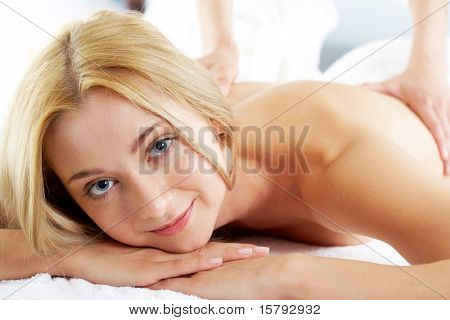 Portrait of calm female looking at camera during procedure of massage