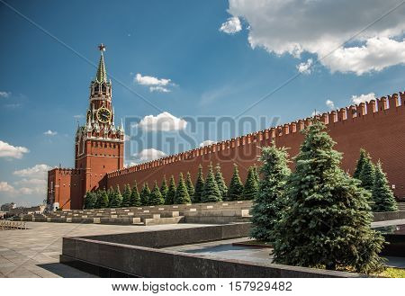 Sunny day at the Red Square with blue sky white clouds green fir-trees the Spasskaya Tower with the Kremlin chimes the main tower with a through-passage on the eastern wall of the Moscow Kremlin