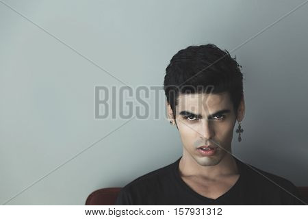 Portrait of attractive modern young white brazilian guy with black hair and cross-earring looking sullenly and saucily gray wall behind