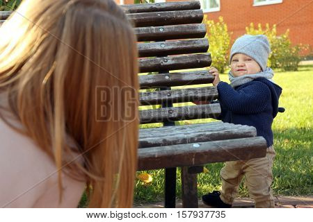 Young woman and cute baby playing at hide-and-seek outdoors