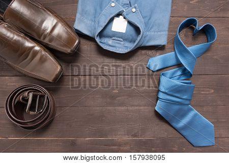 Elegant Set: Brown Men's Shoes, Brown Leather Belt, Blue Shirt, Blue Necktie, On The Wooden Backgrou