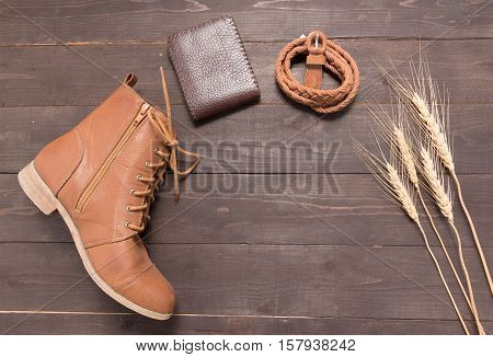 Brown Wallet, Brown Boots And Brown Leather Belt With Rice Bale On The Wooden Background