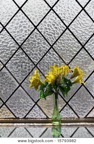 Ramo de flores amarillas en la ventana vitrage