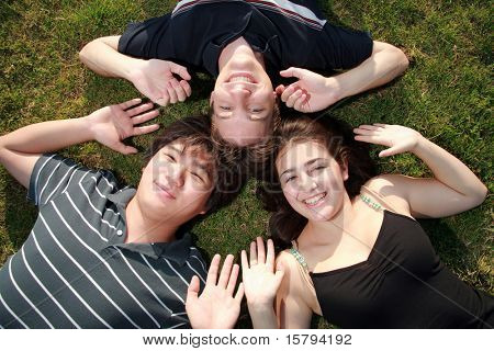 Three happy friends lying on green grass smiling with heads together.