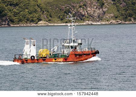 small tug boat sails along the coastline