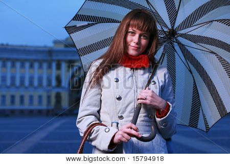Fashion girl with umbrella at Palace Square, St. Petersburg, Russia.