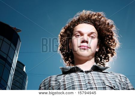 Portrait of a funky young man with curly hair outdoors.