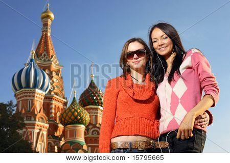 Two beautiful young women next to Saint Basil's Cathedral in Red Square, Moscow, Russia.
