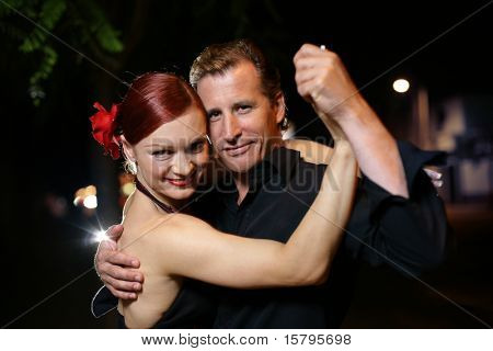 Happy young adult couple dancing outdoors at night, close-up