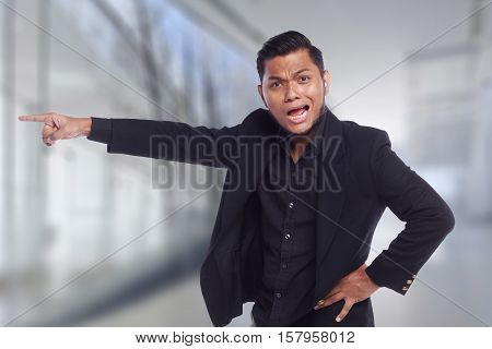 men showing his expression angry face while his finger pointing at the door isolated on white background