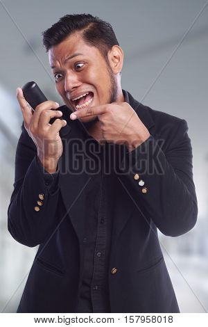 men showing his expression shouting face while he pointing his finger at the phone isolated on white background