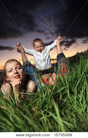 Young family lying in green grass over scenic sunset.