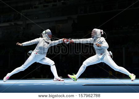 RIO DE JANEIRO, BRAZIL - AUGUST 13, 2016: Ibtihaj Muhammad of United States R and Sofya Velikaya of Russia compete in the Women`s Sabre Team of the Rio 2016 Olympic Games at Carioca Arena 3