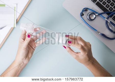 Top view of hands of a female doctor are inserting a pressurized cartridge inhaler into an inhalation chamber on a medical demonstration on her desk - Medical respiratory disease - Focus on the chamber