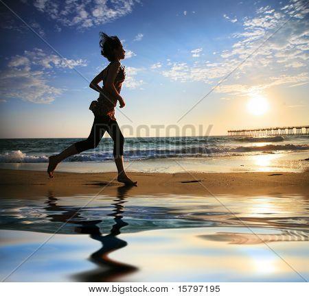 Mujer que corre por la playa de la mar al atardecer