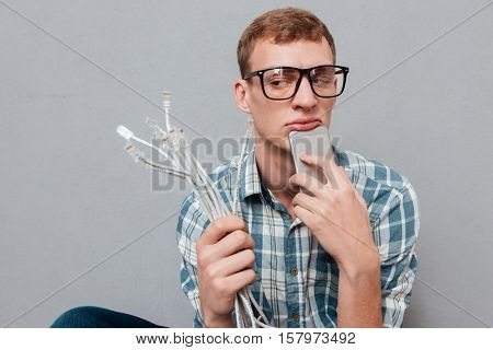 Hipster in glasses with phone and cables. looking away. isolated gray background
