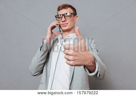 Hipster with phone showing finger up. isolated gray background
