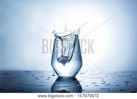 Splash of clear water in a glass with reflection on surface