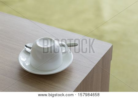 New white cups coffee set upside-down on wooden table.