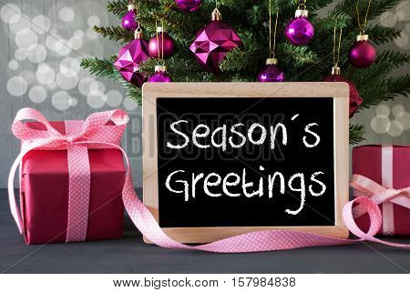 Christmas Tree With Rose Quartz Balls And Bokeh Effect. Gifts Or Presents In The Front Of Cement Background. Chalkboard With English Text Seasons Greetings