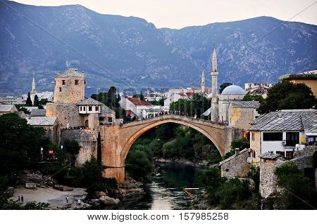 Tourists on the the old bridge of Mostar known as Stari Most at sunset