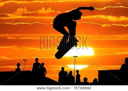 Jumping skateboarder silhouette over scenic sunset sky background