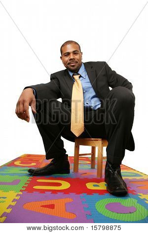 Big African American businessman sitting on small chair over white background.