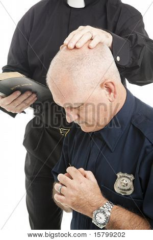 Policeman prays and receives a blessing from his priest or minister.