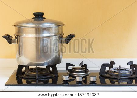 Big hot pot set on gas stove in modern kitchen.