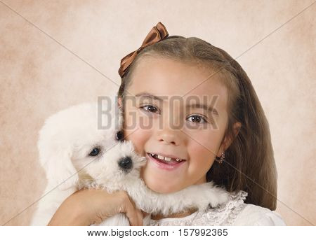 Portrait of pretty little girl with Bichon Frise puppy on a beige background
