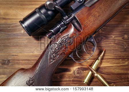 Sniper rifle with bullets on the wooden background
