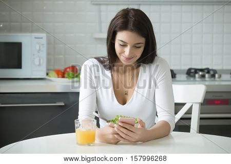 Portrait of smiling young woman sitting at the kitchen table at home or in the modern office with healthy lunch, shifting into a brighter mood as she got cute sms, e-mail