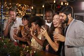 Friends celebrating together at a Christmas party in a bar poster