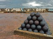 stock photo of cannonball  - Cannonballs stacked neatly on top of a historic Spanish fort - JPG