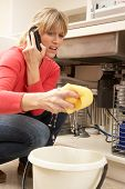 stock photo of plumbing  - Woman Mopping Up Leaking Sink On Phone To Plumber - JPG