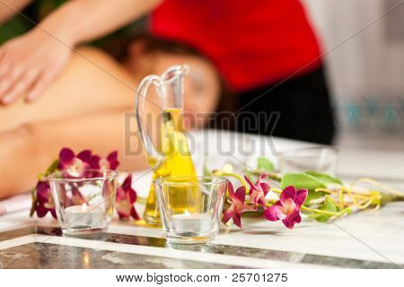 Wellness - woman getting massage in Spa; it is a traditional back massage, focus on massage oil in front