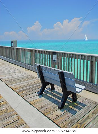 Pier Bench Overlooking Tropical Ocean with Sailboat in Distance